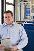 Man on train with newspaper — Stock Photo