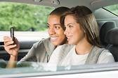 Casal usando telefone celular no carro — Fotografia Stock