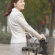 Business Woman standing with a Bicycle — Stock Photo #36634313