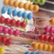 Stock Photo: Looking Through Abacus at Boy Solving Puzzle