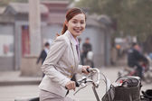 Business Woman standing with a Bicycle — Stock Photo