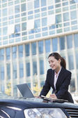 Businesswoman Standing by Car Using Laptop — Stockfoto