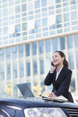 電話を使用して車で立っている女性実業家 — ストック写真
