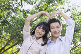 Couple Making a Heart Shape with Their Arms — Stock Photo