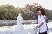 Coppia puntando da un lago — Foto Stock