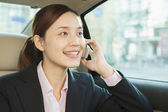 Businesswoman in Back Seat of Car on the Phone — Stock Photo