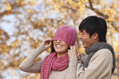 Man Covering a Woman's Eyes with Hat — Stock Photo