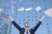 Businessman throwing paper with arms in the air — Stock Photo