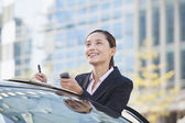 Businesswoman Standing by Car Using Phone — Stock Photo