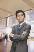 Businessman with arms crossed at the airport — Stock Photo