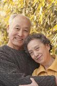 Senior couple under trees — Stock Photo
