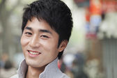 Man smiling and looking at camera outdoors — Stock Photo