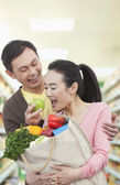 Man Feeding Woman Apple in Grocery Store — Stock Photo