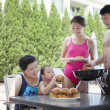 Family barbequing by the pool on vacation — Stock Photo