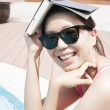 Woman by the pool holding a book over her head — Stock Photo