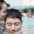 Woman kissing man in the pool — Stock Photo