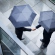 Businessmen shaking hands in the rain — Stockfoto