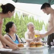 Family eating hamburgers by the pool — Stock Photo