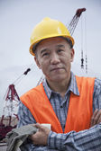 Worker outside in a shipping yard, crane in the background — Stock Photo