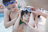 Family helping son put on goggles — Foto Stock