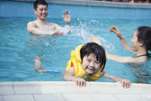 Smiling son in the water with family in the background — Stock Photo