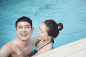 Сouple smiling and relaxing in the pool — Stock Photo