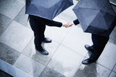 Businessmen shaking hands in the rain — Stock Photo