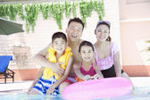 Family smiling by the pool — Stock Photo