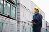 Worker examining cargo in a shipping yard — Stock Photo