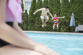 Father and daughter holding hands and jumping into the pool — Stock Photo
