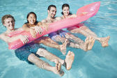 Friends in the pool with an inflatable raft — Stock Photo