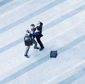 Businessmen fighting each other of the sidewalk — Stock Photo