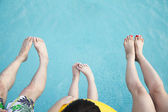 Feet on young family in the pool — Stock Photo