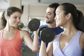 Fitness instructor helping two young women lift weights — Stock Photo