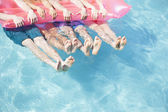 Friends in a pool holding onto an inflatable raft with feet sticking out of the water — Stock Photo