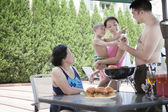 Family barbequing by the pool on vacation — Foto Stock