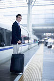 Businessman with a suitcase on the railroad platform — Stock Photo