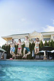 Friends jumping into a pool — Stock Photo