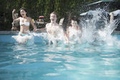 Friends jumping into a pool, mid-air — Stock Photo