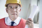 Architect holding a rolled up blueprint indoors — Stock Photo