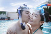 Couple kissing on the cheek in the pool — Stock Photo