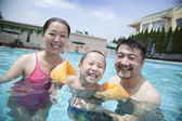 Young family in the pool on vacation — Stock Photo