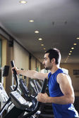 Muscular man exercising on a cross trainer — Stock Photo