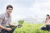 Man holding plant and gardening with young woman — Stock Photo