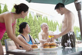 Family eating hamburgers by the pool — Foto Stock