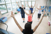 People with hands in the air in a yoga class — Stock Photo