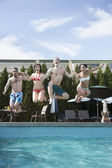 Friends holding hands and jumping into a pool — Stock Photo