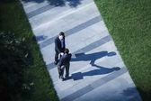Businessmen shaking hands on the sidewalk — Stock Photo