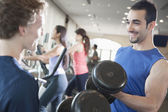 Men smiling and lifting weights in the gym — Stock Photo