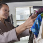 Woman going through clothes at fashion store — Stock Photo #36656909